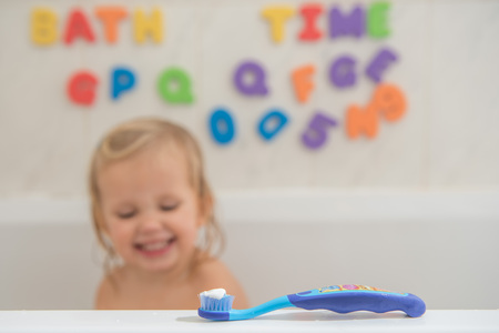 Toothbrush close-up  with smiley little girl having bath in background . Close-up photo. Teeth cleaning, dental care. Banque d'images