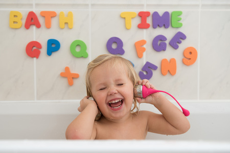 Happy little girl taking a bath and playing with tea infusers as a headphones . Beautiful wide smile of little girl with great healthy white teeth.Water fun for kids.