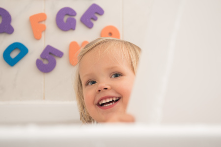 Happy little girl taking a bath and playing peekaboo with parent.Beautiful wide smile of little girl with great healthy white teeth