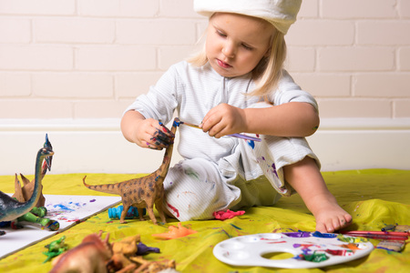 Little girl concentrating whilst painting dinosaur figure Banque d'images