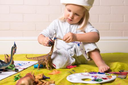 Petite fille se concentrant tout en peignant la figure de dinosaure