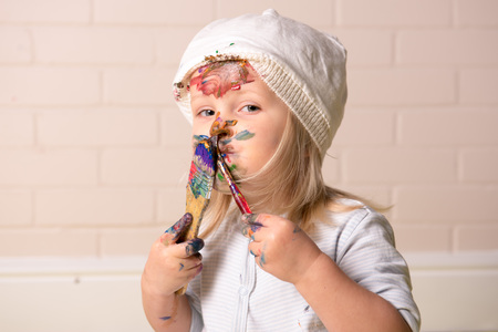 Little girl having fun painting her face with colourful paints and looking at the camera. Childhood fun. Banque d'images