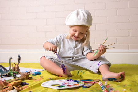 Little girl having fun whilst painting her feet using colorful paints. Childhood fun.