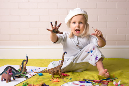 Little Girl having messy play with paints  and showing colorful painted hands. Banque d'images