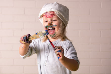 Little girl having fun covering herself with colorful paints. Childhood fun. Banque d'images