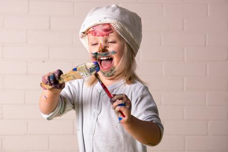 Petite fille s'amuser à se couvrir de peintures colorées. Amusement d'enfance. Banque d'images