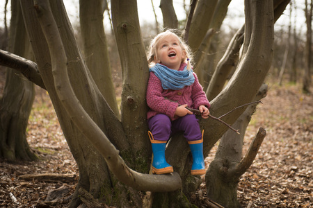 Cute toddler girl having fun on tree in the forest.