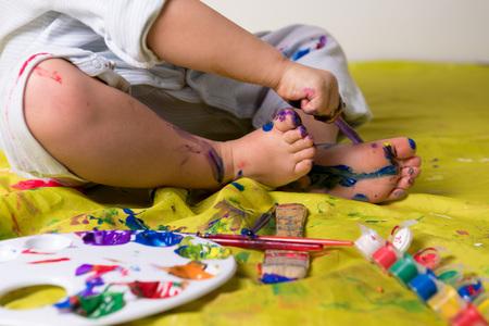 Les petits pieds de peinture à l'enfant à l'aide de peintures colorées.