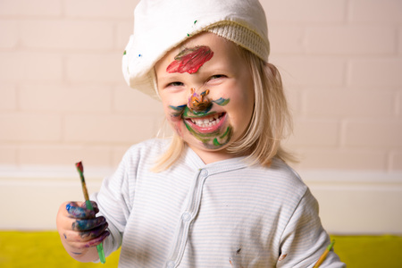 Happy little girl having fun painting face with colorful paints. Childhood fun