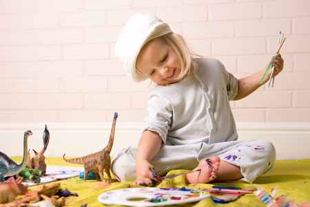 Petite fille se amuser tout en peignant ses pieds avec des peintures colorées. fun enfance. Banque d'images
