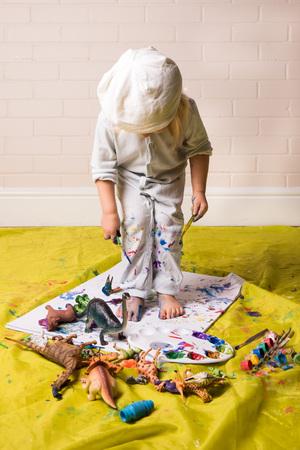 Enfant jouant avec des peintures et des jouets Banque d'images