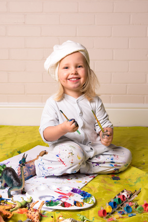 Happy little girl having messy play and  looking at the camera whilst painting. Childhood fun. photo