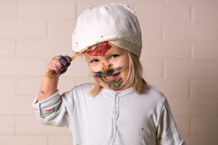 Happy little girl having fun painting face with colorful paints. Childhood fun.