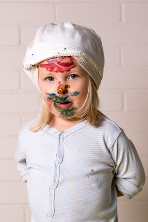 Little girl with painted face looking at the camera. Innocente face. photo