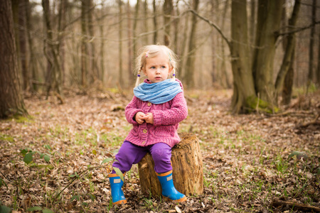 Thoughtful toddler girl in the wood sitting on the stump