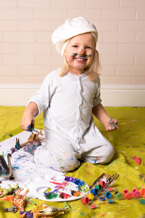 Happy little girl having messy play and  looking at the camera whilst painting. Childhood fun.