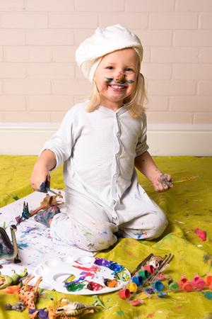 Bonne petite fille ayant un jeu en désordre et regarde la caméra tout en peignant. Amusement de l'enfance.
