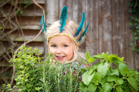 Happy little girl in colorful Indian headband standing in the garden surrounding by fresh green herbs Banque d'images