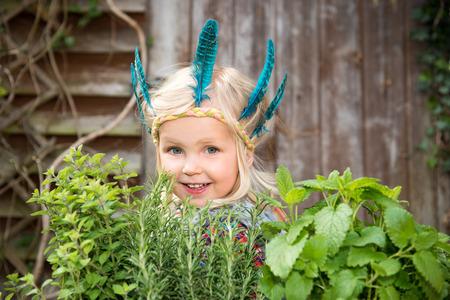 Heureuse petite fille en bandeau indien coloré debout dans le jardin qui entoure de fines herbes vertes