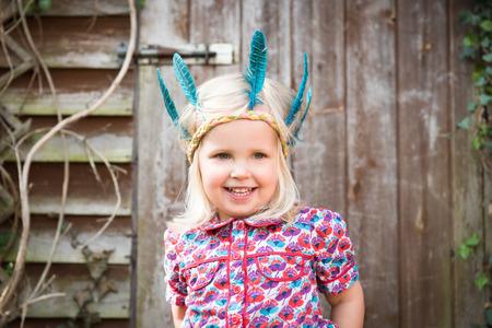 Happy little girl in colorful Indian headband standing in the garden Banque d'images