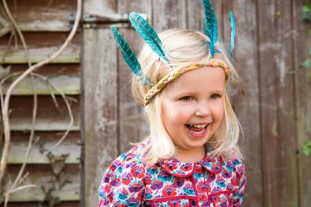 Heureuse petite fille en bandeau indien coloré, debout dans le jardin Banque d'images