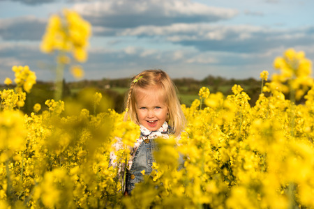 Happy girl smiling in yellow blossoming rapeseed field Banque d'images