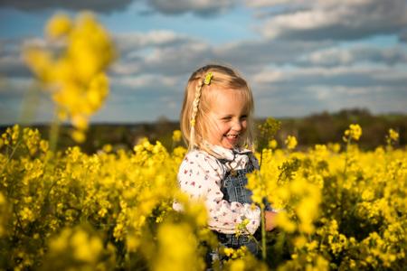 Fille heureuse, souriant dans le champ de colza floraison jaune