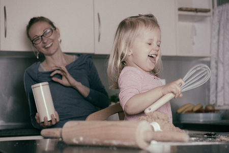 Mother and little toddler daughter having fun whilst baking in the kitchen. Instagram effect.