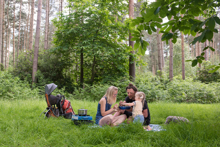 Happy family having dinner in woodland.Camping family concept. Banque d'images