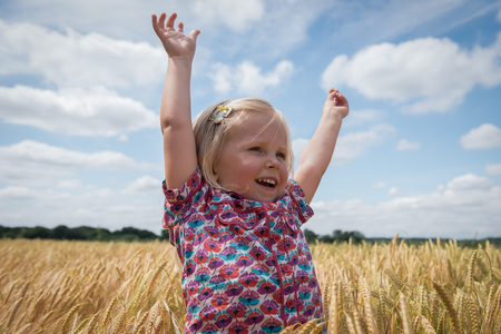happy little girl with arms raised