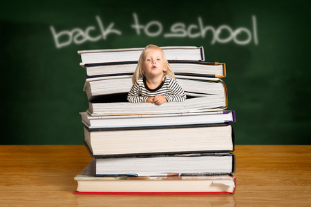 Blond girl wearing stripped top, popping out of the pile of books in the classroom