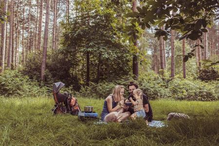 Famille heureuse en train de dîner dans un concept de famille woodland.Camping. Banque d'images