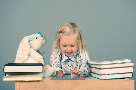Mignonne petite fille lisant des livres à son ami de lapin. Concept éducatif.