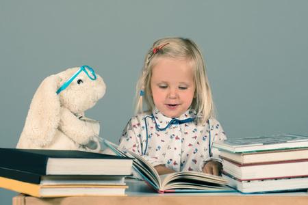 Cute little girl reading books. Educational concept.