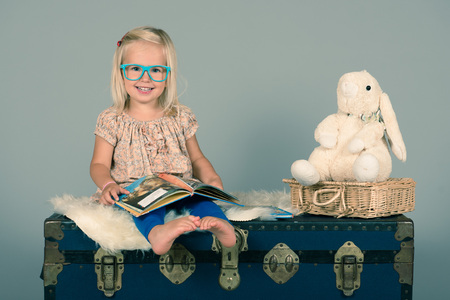 Cute preschool girl reading  book for her little friend Rabbit