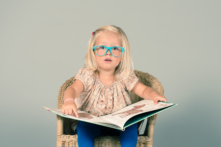 Cute little girl siting on the chair and reading big book with excitement
