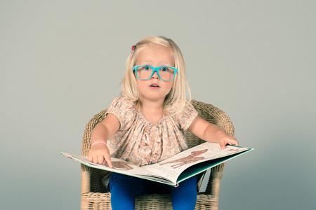 Mignonne petite fille située sur la chaise et lisant un gros livre avec excitation Banque d'images