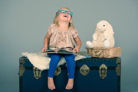 Mignon, fille heureuse s'amuser tout en lisant un livre pour son petit ami Lapin