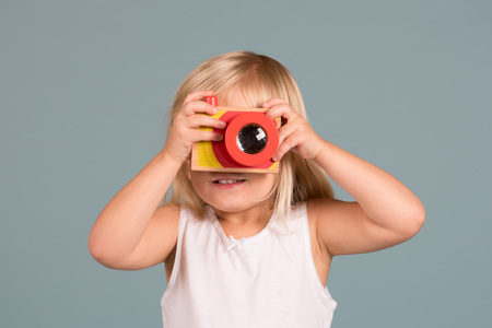 Portrait of toddler girl taking photo using wooden camera toy Banque d'images
