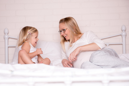 Pregnant young mother and her daughter having fun in the bed Banque d'images