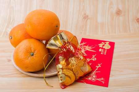 variable: Chinese New Year - Mandarin orange, gold sycee (Foreign text means wealth) and red packet (Foreign text means spring season) on white painted wood table