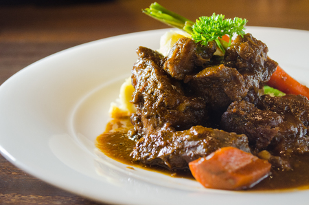 Beef stew, served with sided vegetables and mashed potatoes. Selective focus Stock Photo
