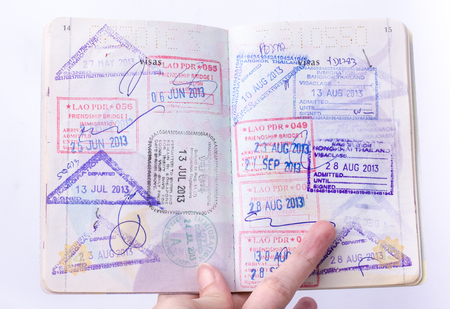Opened passport with visa stamps on the pages Editorial