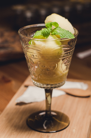 Mango ice cream in a glass. Placed on a wooden table
