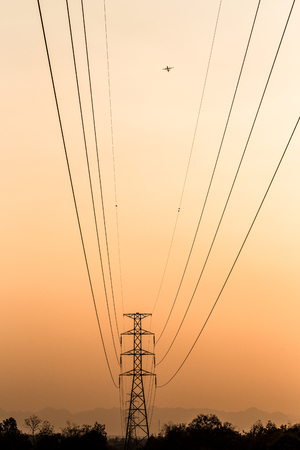 electrical tower: Silhouette of electrical tower with airplan Stock Photo