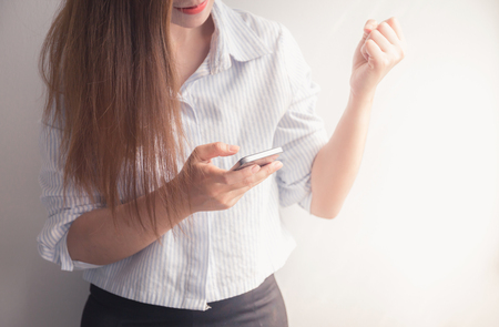 busy person: Working woman happy with her successful on phone Stock Photo