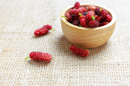 floor cloth: Red mulberry in wooden bowl and on cloth floor, healthy fruit Stock Photo