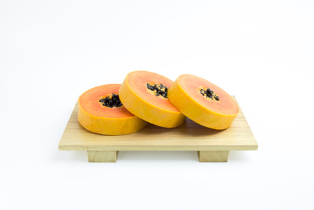 Isolated yellow ripe papaya on wood plate on white background, include clipping path Stock Photo