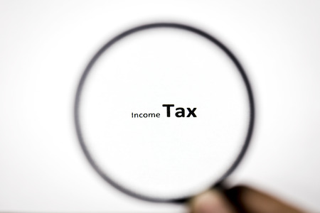 tax bracket: Looking Income Tax word through the magnifier Stock Photo