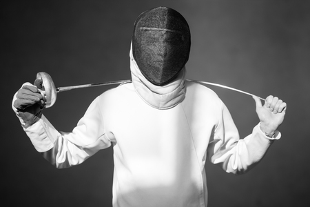 fencer in the sports room in a mask and with a sword in a hand. the fencer prepares for competitions. fencing coach. fencing sport motivation. mask and sword